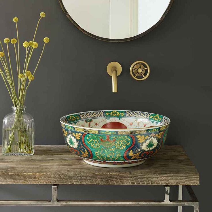 Multi-coloured porcelain basin. The outside of the bowl is decorated with intricate patterns against an emerald-green and dark blue background, to complement the contrasting design of festive balloons on a white background inside the basin. The touches of gold catching the light add to the Adriana's sophisticated chic. https://www.decoralist.com/product/adriana-basin/