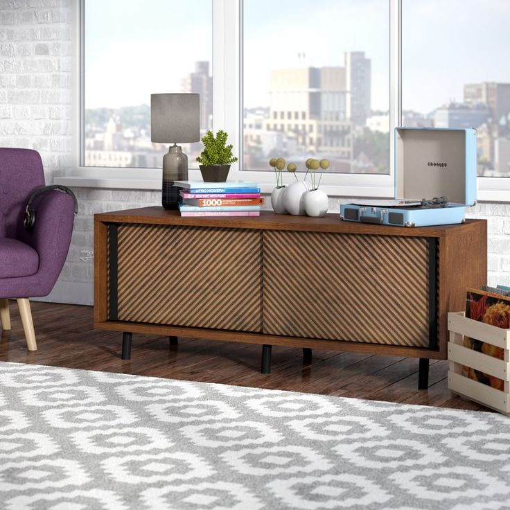 Drawing inspiration from Danish modern design, this charismatic credenza lends minimalist appeal to your dining room or den. Made in the USA from manufactured wood in a grand walnut finish, this dapper design features a simple rectangular silhouette and six straight, round legs. Two sliding doors showcase a decorative diagonal groove design adding dimension and depth, while the two interior cabinets include adjustable shelves to accommodate serveware, stemware, and fine china place settings…