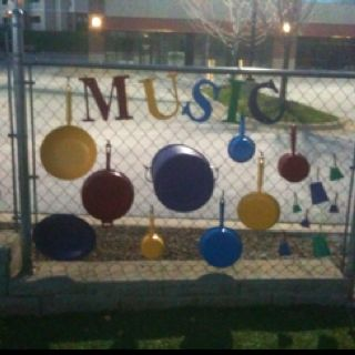 "Music center for preschool playground. Spray paint pots and pans and hang them along the fence. Let the students explore with different ""drum sticks."" They could make music with their hands, hard sticks, or soft covered sticks. Let them discover what creates different noises."