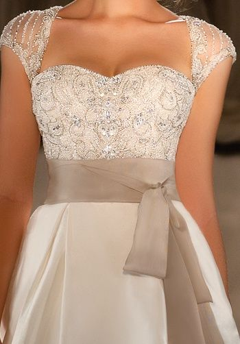 The beading and detail on this dress is gorgeous love the sweetheart neckline and sheer cap sleeve the sash is a nice touch.