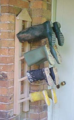 DIY hanging (wall-mounted) boot rack with 4 pairs of boots on it