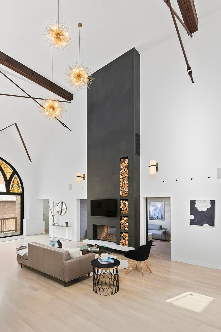 Painting the fireplace and chimney a dark gray helps pull the eye up through this vast airy living room. The crowning glory is the starburst pendant lights twinkling overhead.