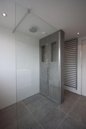 Badkamer mooie kraan en douches. Tegels verticaal net grafzerk.