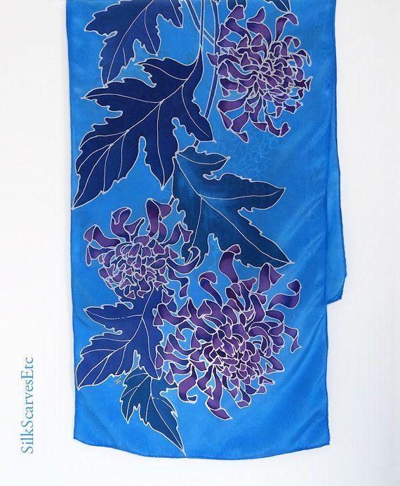 Cette main bleue peint caractéristiques de foulard en soie crêpe de chine chrysanthèmes pourpres avec des feuilles bleus foncé. Soie, Crêpe de chine est une soie de poids moyen, il a un éclat mat gentil. Il mesure environ 14 x 57 il a main traditionnelle laminée ourlet. Sil vous plaît voir plusieurs de mes foulards floral peint à la main à https://www.etsy.com/shop/SilkScarvesEtc/search?search_query=floral+scarf&order=date_desc&view_type=gallery...