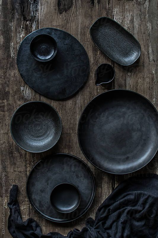 Black crockery, plates, bowl, linen on a wooden background Download this high-resolution stock photo by KEMA FOOD CULTURE from Stocksy United.
