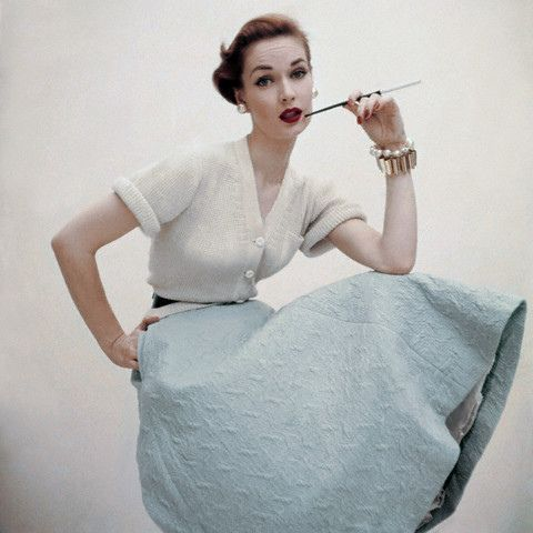ca. December 1951, New York, New York, USA — Model wearing separates by Greta Plattry: white ribbed knit, wool cardigan sweater with robin's egg blue, knit skirt.