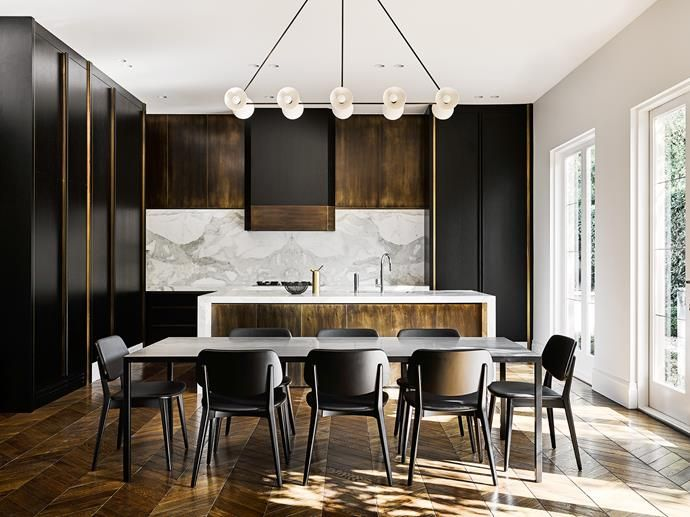 The kitchen joinery is a rich synergy of clean American oak with a black two-pack lacquer finish and honed Calacatta kickers.     Photo: Brooke Holm & Sharyn Cairns   Styling: Marsha Golemac   Story: Belle