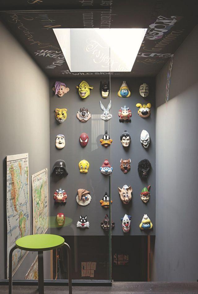 Dans une cage d'escalier, tous les pans de murs peuvent être exploités. Ici on a opté pour des murs peints en noir intense pour mieux mettre en valeur les masques de personnages de dessins animés et les cartes anciennes exposés façon cabinet de curiosité.