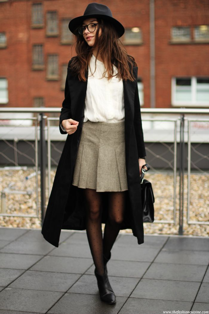 Beatrice Gutu is wearing a black long coat from Chicwish, white top from Fashion Pills tweed skirt from Benetton, hat from MissGuided and the ankle boots are from Zara