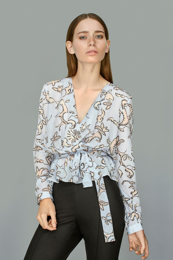 Avina Augusta is a feminine top in an exclusive print. The top has long sleeves and a drawstring waist.