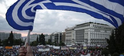 A protester waves a Greek flag during an anti-austerity rally in front of the parliament building in Athens, Greece on June 21, 2015. (photo: AP)