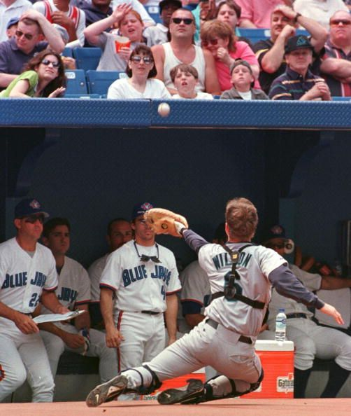 Seattle Mariners' catcher Dan Wilson slides into the Toronto Blue Jays dugout as he catches a Jose Canseco pop up in the first inning at Toronto's...