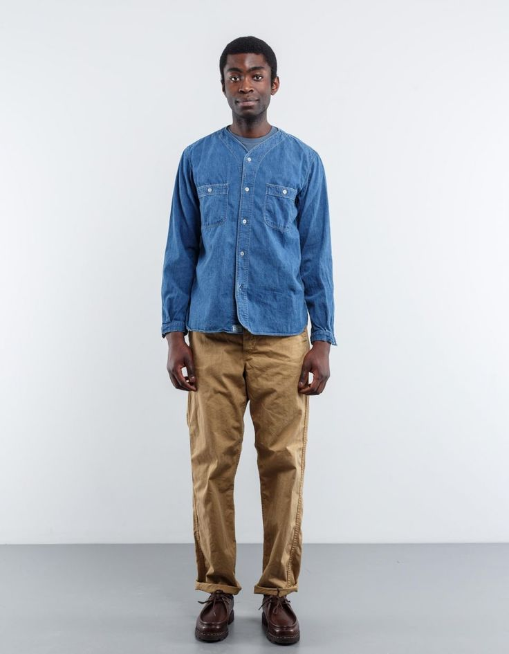 No Collar Denim Inner Shirt from Orslow. V-neck shirt with a button placket. Two chest pockets, buttons at cuff and slightly rounded bottom hem. Blue 100% Cotton Made in Japan Model is 188 cm tall, measures 91 cm over chest, 88 cm around the waist and wears size 3