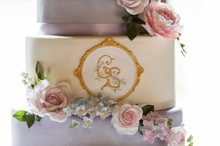Pretty Lilac & Ivory Wedding Cake. Sugar Roses, Hydrangeas, Peonies and small blossoms. Gold Monogram & Bespoke Bride and Groom