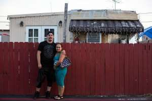 Jose Luis Vernal and his partner Rosa Muñoz pose for a portrait outside their home in El Cajon, California.