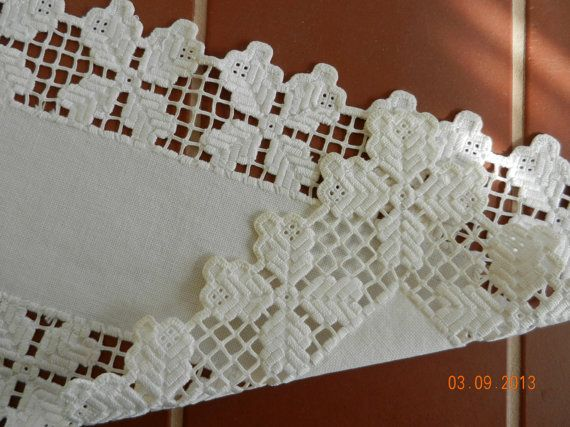 Ivory colored linen table runner with white cut-work edging. The thread used in edging looks and feels like cotton sheen. Hardanger embroidered edge.    19 long, 8 wide. There is a tiny light coffee colored spot on the tip of one of the edging picots, which is shown is the 3rd photo. After photographing, I dabbed at it with a damp white towel and mild soap and it did disperse quite a bit. It may come out completely with a good soak. Other than that, this pretty runner is in pristine…