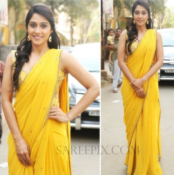 """Actress Regina cassandra in yellow georgette saree photos at """"Big FM"""". Embroidery corset sleeveless blouse and one-side swept curly hairstyle finished her"""