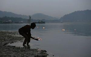 Um menino flutua lâmpadas de barro do rio Brahmaputra, na Índia