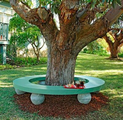 Love this bench around a shade tree using large boulder rocks as the seat stands!