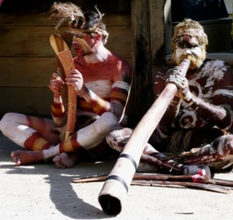 Aborigines playing the didgeridoo and clap-stick.