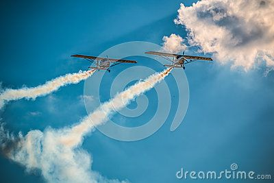 A team of two airplanes flying together high up in the sky on an air show. Airplanes on air show with smoke trails. Airplane performing difficult maneuver in the sky. Blue sky clouds and trails. Blue background.
