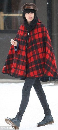Style stealer: Agyness Deyn takes a walk through the snow in New York wearing a red and black poncho and John Lennon in a similar style on t...