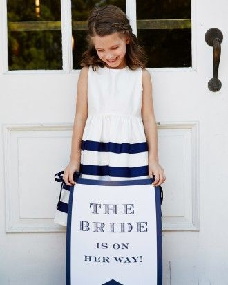 Queue signage (and an adorable flower girl) at your wedding. Get more ideas online from this tennis-themed celebration!