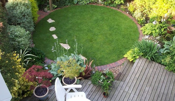 Clever use of decking adds space to a tiny place Small circular lawn with brick edge, with compact shrub planting and raised deck area for seating.
