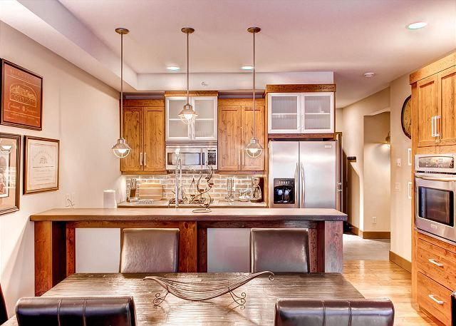 Big White Vacation Rental - Open plan dining and kitchen area in this lovely and luxurious residence, ideal for a family. The interior design is stunning with hardwood heated floors and tumbled sandstone, and a heat recovery ventilation system (great for allergy sufferers).