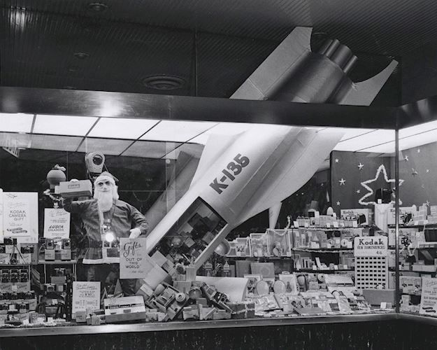 Black and white photograph of a product display in the Kodak Australasia Pty Ltd store in Sydney, New South Wales, circa 1950s. The display features a large rocket crashing into a pile of various Kodak products. There are also some Kodak products inside the rocket. A Santa Claus / Father Christmas dummy is next to this, holding a box of Verichrome film and a sign that says 'Gifts From Out of This World for You'.  Sydney, 1957