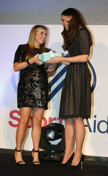 Catherine, Duchess of Cambridge, patron of SportsAid charity, presents the charity's this year's One-to-Watch Award to shooter Amber Hill, 16, at the SportsBall, the charity's annual gala dinner at Victoria Embankment Gardens on November 28, 2013 in London, England.
