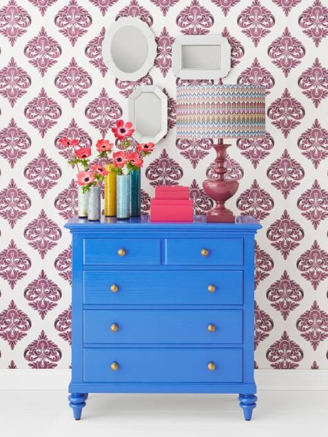 """In a perfect mash-up of romantic and modern, a Venetian blue dresser gets paired with temporary damask wallpaper and dainty mismatched mirrors. Grouped en masse, ceramic bud vases are a clever way to show off a bouquet. Lamp: Style Craft Tween 27½""""-tall high-gloss table lamp in wine with drum shade, $90, wayfair.com"""