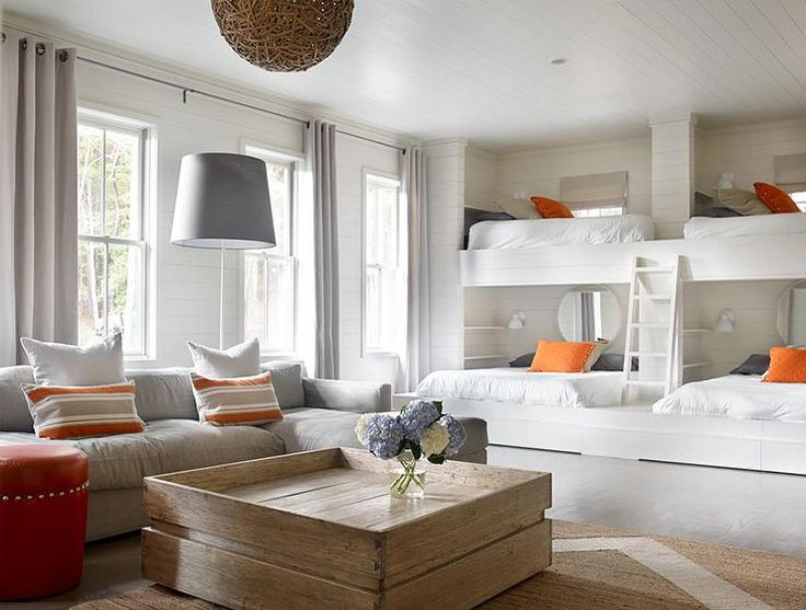Country bunk room features a shiplap walls lined with a wall of side by side built-in bunk beds dressed in orange and gray pillows fitted with a built-in ladder.