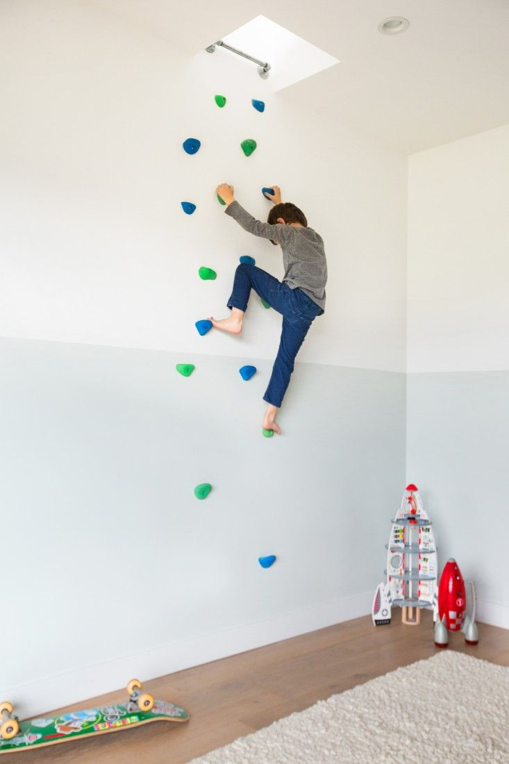 Boy on climbing wall in bedroom with two-toned walls in Murnane House in Los Angeles by Project M Plus | Remodelista