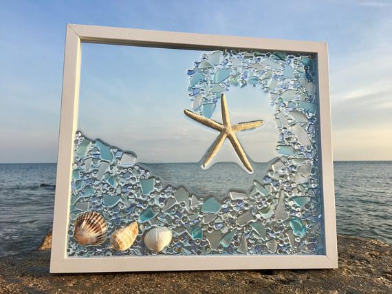 Beautiful white framed sea wave sun catcher. Done with natural sea glass in shades of blue. These sun catchers are best hung in a window, on a light colored wall or back lit to get the full effect from the light shining thru the beach glass. The design is fused on the glass not glued.