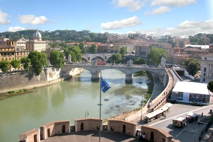 Hop on-off bus crossing a bridge in Rome