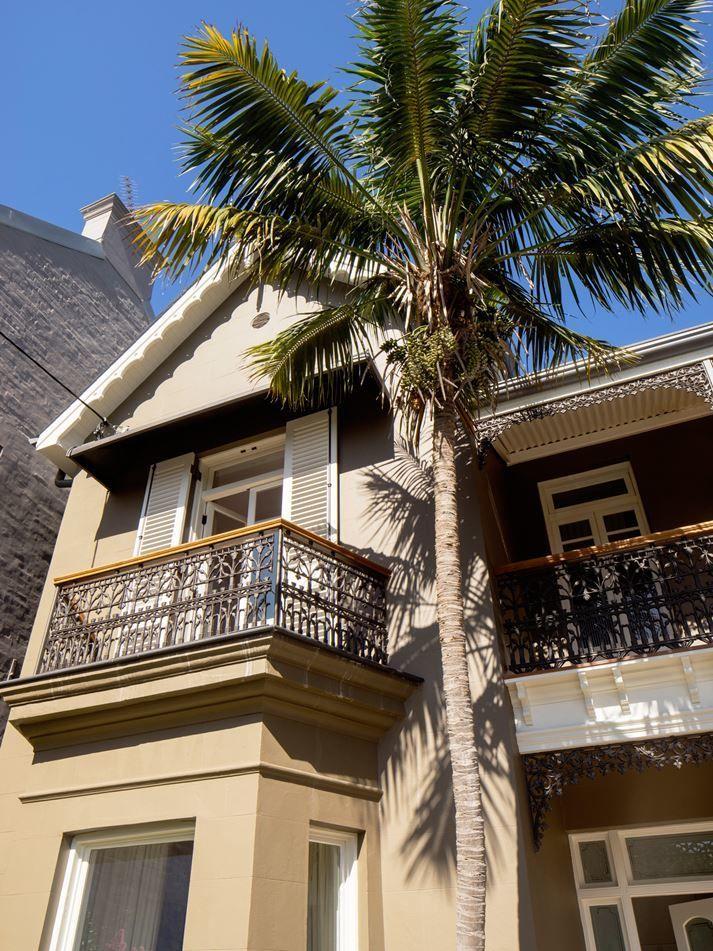 Восстановленный фасад здания оригинальной чугунной ковкой и резными деревянными узорами.  (викторианский,современный,архитектура,дизайн,экстерьер,интерьер,дизайн интерьера,мебель,фасад) .