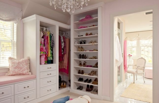 Light pink closet and dressing room with window seat, chandelier, and adjoining vanity.
