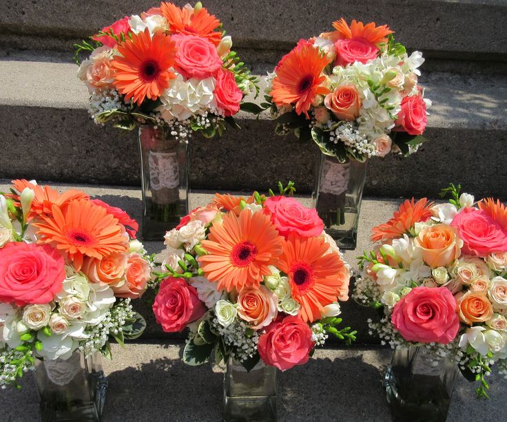 Coral, peach and white wedding bouquets including freesia, hydrangea, gerbera daisies, and roses. Designed by Brittany