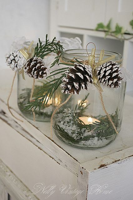 DIY::Fill large jars with greenery, fake snow, and candles - tie pinecones on with twine.