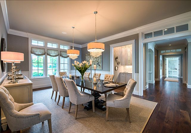 This neutral dining room is full of interest and beauty. Notice the transoms in the large hallway, the butler's pantry and the double chandeliers above the dining table.