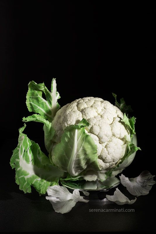 Cauliflower with garlic skin.  A cauliflower on a round metal platform with garlic skin on a black background. Part of my Personal Project, you can see more works on my blog foodfulife.com