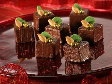 Sacher kostičky     100 gramů hořká čokoláda 120 gramů mleté ořechy 60 gramů hladká mouka 20 gramů kakao špetka mletá skořice špetka mletý hřebíček 150 gramů rostlinný tuk Hera 120 gramů krystalový cukr 4 kusy vejce   náplň, zdobení      180 gramů horká meruňková marmeláda 200 gramů dortová čokoládová poleva 4 lžíce olej celé pražené mandle zlaté perličky, marcipánové listy