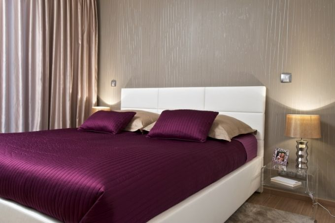 Ložnici zútulňuje tapeta v přírodním odstínu a další textilie barevně i stylově navazující na hlavní obytný prostor. Transparentní noční sto...