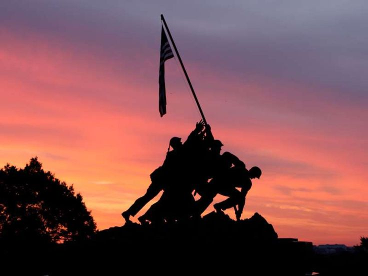 The sunrise warms the sky about the Iwo Jima Memorial, - AP Photo/Ron Edmonds