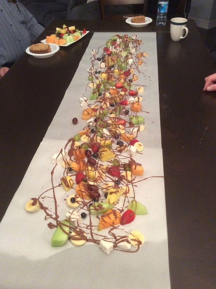 Dessert époustouflant : fruits frais, guimauves posés sur un chemin de table en papier et arrosés de chocolat fondu.