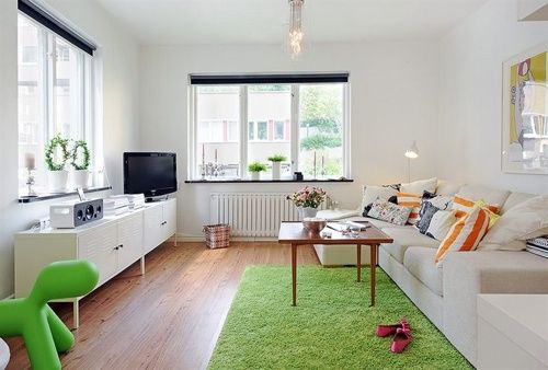 12 White Rooms with Pops of Color: Alvhem Makleri (or, for English only speakers, Alvhem Estate & Interior) is the source of this casual living room. Furnished with an IKEA locker console, contemporary white sofas, a vintage coffee table, and lime green rug, it looks easy to replicate, and affordable.