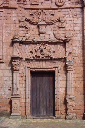 Ornate stonework surrounds this simple wood door which serves as the entrance to a Jesuit mission in Paraguay. doors of the world.  travel. South America.