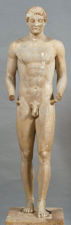 Funerary statue of a kouros. Found in the Mesogeia, Attica. The hair on the forehead is chipped, as are the eyes, nose and mouth. Preserved together with its low rectangular base, on which the name of the deceased Aristodikos is inscribed. The top part of the head has not been polished. The hair is short, the arms are no longer attached to the thighs and the left leg is advanced. This piece is considered a landmark in the development of sculpture, and is the last in the kouros series…