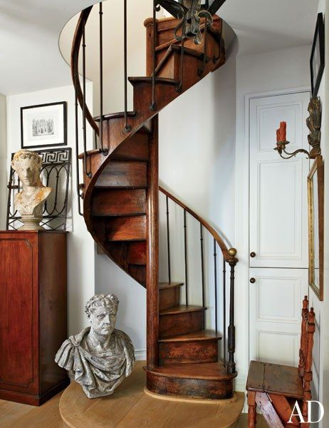 A circa-1840 French spiral staircase leads from a second-story hallway to the guest loft | archdigest.com